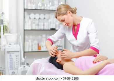Doctor beautician doing facial massage in the spa salon. The procedure of facial massage in beauty salon. Face Skin Care. Cleansing Procedure. Cosmetology.