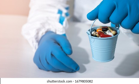 A doctor in a biological suit and blue gloves holds a small bucket filled with colorful pills