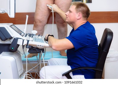 Doctor in a blue coat with a clinic with diagnostic equipment. Surgeon man performs an ultrasound using a device on the legs of a female patient. Medical tools in hospital.