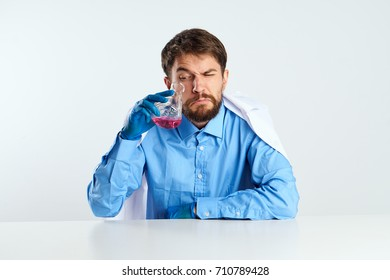 doctor in blue shirt and medical robe sitting at the table holding a flask with a pink liquid on a light background