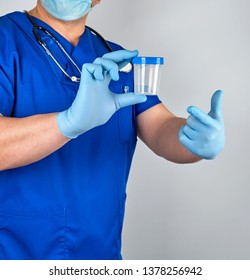 doctor in blue uniform and latex gloves is holding an empty plastic container for taking urine samples,  gray background