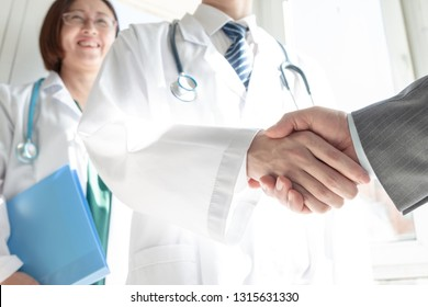 Doctor and business people shaking hands
