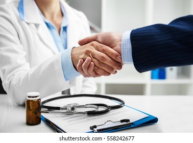 Doctor and businessman shaking hands in the office. Concept of cooperation and agreement.