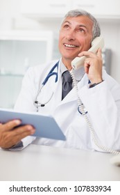 Doctor calling while holding a tablet computer in medical office