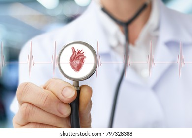 Doctor the cardiologist listens to the heart on blurred background.