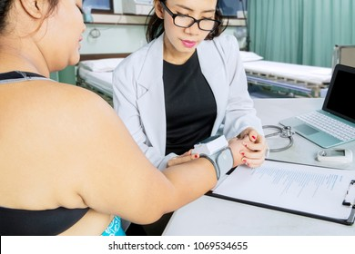 Doctor cardiologist measuring blood pressure of her fat patient while sitting in the hospital