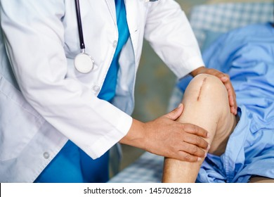Doctor check Asian senior or elderly old lady woman patient scars surgical total knee joint replacement Suture wound surgery arthroplasty at nursing hospital ward : healthy strong medical concept.