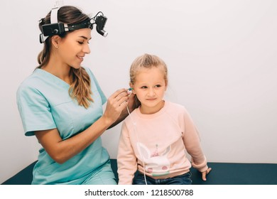 doctor check a girl's ears. Little girl having hearing test , procedure impedance audiometry