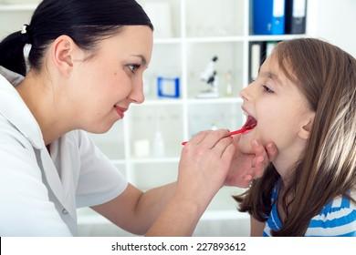 Doctor check throat of little girl.