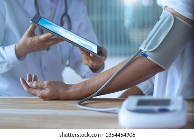 Doctor checking blood pressure and gives advice to older patient via tablet on hands in hospital background, healthy technology (IoT). Elderly health concept.