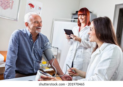Doctor Checking Blood Pressure To A Mature Man At Doctor's Office.