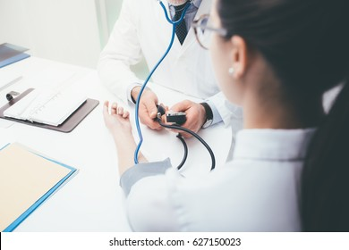 Doctor checking blood pressure of a patient, he is measuring heart pulses with a sphygmomanometer, healthcare and diagnostics concept