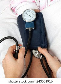 Doctor checking blood pressure with stethoscope
