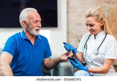 Doctor checking blood sugar level with glucometer of senior man. Diabetes test. Healthcare concept.