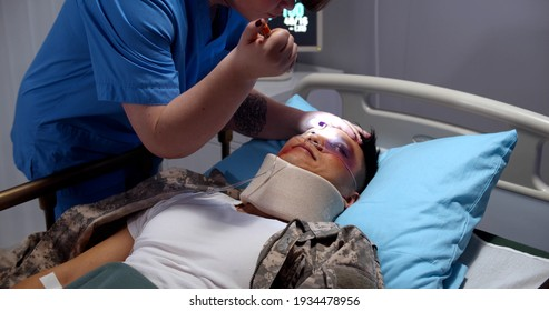 Doctor checking condition of unconscious injured soldier in hospital ward. Army hospital nurse with flashlight examining military officer with injured neck and bruises