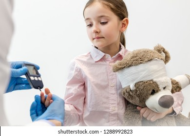 Doctor checking diabetics on equipment of girl with teddybear at clinic