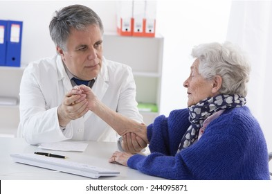 Doctor checking elderly female patient's injured arm