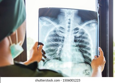 Doctor checking examining chest x-ray film of patient at ward hospital.