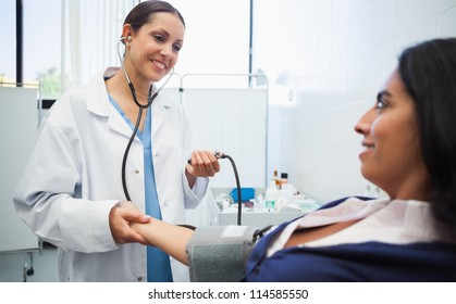 Doctor checking female patients blood pressure in hospital room