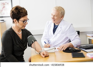 Doctor Checking Female Patient's Blood Pressure