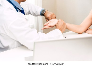 Doctor checking female patient's pulse in hospital.healthcare and medicine