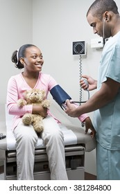 Doctor checking girls blood pressure