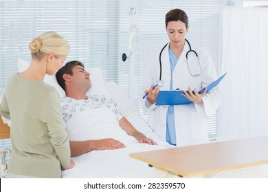 Doctor checking her patient in hospital room