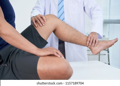Doctor checking leg of patient with acute pain