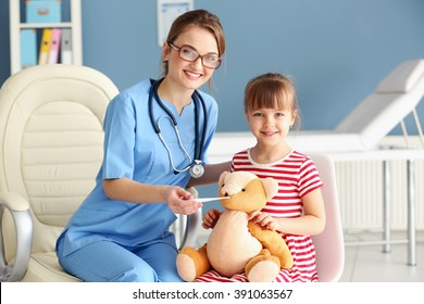 Doctor checking little girl's temperature
