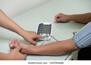 Doctor checking man's pulse and measuring blood pressure at table in hospital, closeup