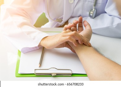 Doctor is checking patience's pulse by fingers, medical checking on table. Asian doctor