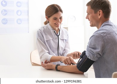 Doctor checking patient's blood pressure in hospital. Cardiology concept