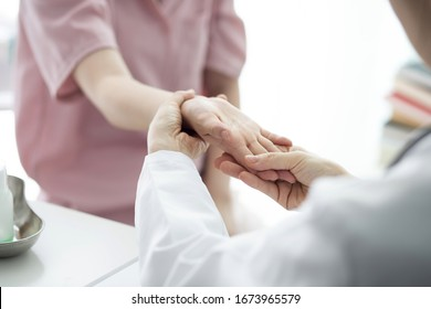 Doctor checking patient's hand pain