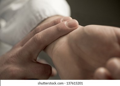 A doctor checking a patients wrist for their pulse