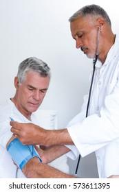 Doctor checking senior mans blood pressure in hospital