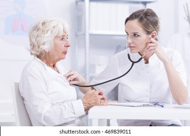 Doctor checking senior patient's breath sound with a stethoscope