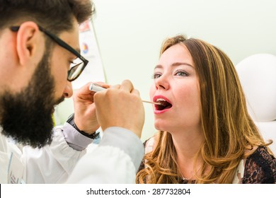 doctor checking throat on young female patient