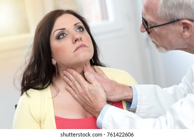 Doctor checking thyroid of a young patient, light effect