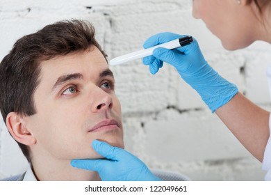 Doctor checking tired eyes of patient