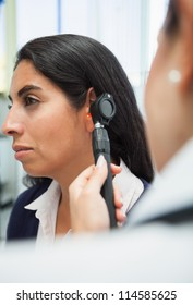 Doctor checking womans ear with otoscope in hospital