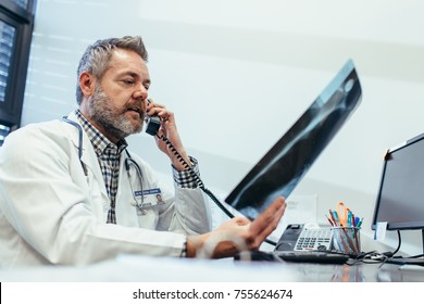 Doctor checking a x-ray report and talking on phone at clinic. Radiologist working at his office desk.