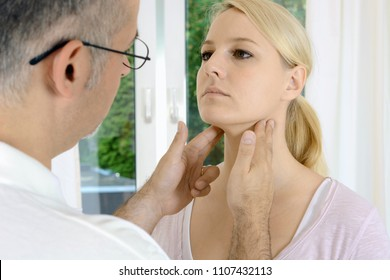 Doctor at checkup palpates lymph nodes in female patient