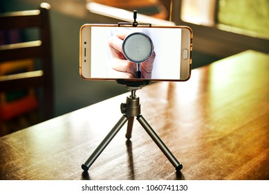 Doctor checkup in smartphone on a tripod in living room