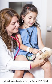 Doctor and child paying with a stuffed animal and stethoscopes