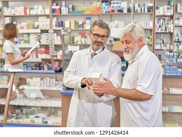 Doctor choosing medicines with patient in drugstore. Professional specialist helping elderly man with medicaments. Pensioner holding medical box. Pharmacist standing near shelves with medicines.
