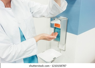 Doctor cleaning and disinfecting her hands in hospital diligently