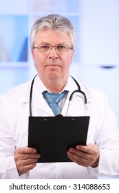 Doctor with clipboard at workplace