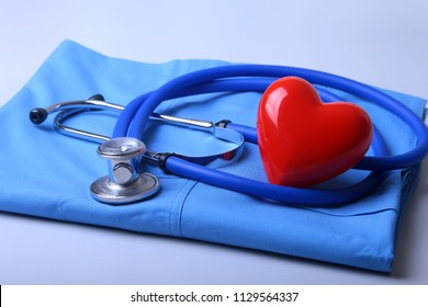 Doctor coat with medical stethoscope and red heart on the desk