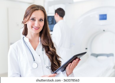 Doctor with colleagues standing in hospital at CT machine with scan results