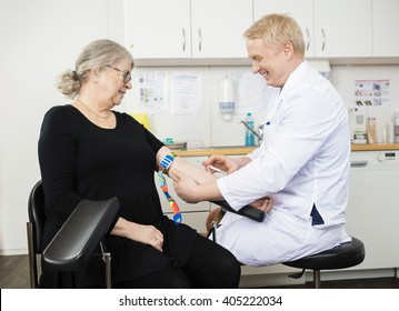 Doctor Collecting Senior Patient's Blood For Test In Hospital